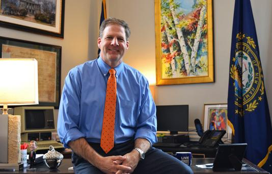 Governor Sununu sitting on the corner of his desk